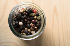 Mixed Peppercorns in Glass Container on Light Wood Background Royalty Free Stock Images