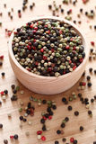 Mixed peppercorns in a wooden bowl. Close-up Royalty Free Stock Photography