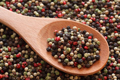 Mixed peppercorns in a wooden spoon. On a mixed peppercorn background. Close-up Stock Images
