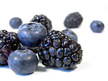 Mixed pile. Closeup of blueberries and blackberries isolated on white stock photography