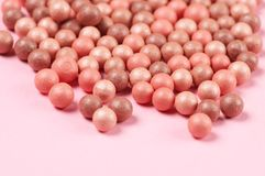 Face pearls blush. Mixed pink and tan colored glow face pearls blush close-up on pink background. Shallow DOF Royalty Free Stock Images