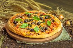Mixed pizza with chicken, pepper, olives, onion, basil on pizza board. Close up view of baked homemade piza. Rustic pizza home made food. Tasty pizza with royalty free stock photos