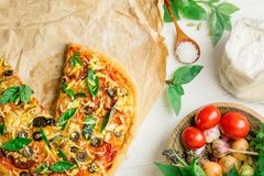 Tasty pizza with vegetables and basil. Mixed pizza with chicken, pepper, olives, onion, basil on pizza board. Close up view of baked homemade piza. Rustic pizza royalty free stock image