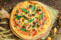 Mixed pizza with chicken, pepper, olives, onion, basil on pizza board. Close up view of baked homemade piza. Rustic pizza home made food. Tasty pizza with royalty free stock image