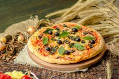 Tasty pizza with vegetables and basil. Mixed pizza with chicken, pepper, olives, onion, basil on pizza board. Close up view of baked homemade piza. Rustic pizza stock images