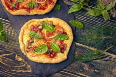 Tasty pizza with vegetables and basil. Mixed pizza with chicken, pepper, olives, onion, basil on pizza board. Close up view of baked homemade piza. Rustic pizza royalty free stock photos