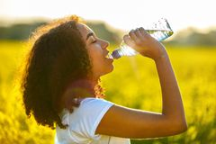 Mixed Race African American Girl Teenager Drinking Water royalty free stock photography