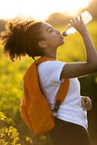 Mixed Race African American Girl Teenager Drinking Water at Suns. Outdoor portrait of beautiful happy mixed race African American girl teenager female young Stock Images