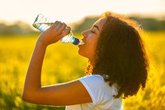Mixed Race African American Girl Teenager Drinking Water at Sunset stock photo