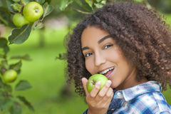 Mixed Race African American Girl Teenager Eating Apple. Outdoor portrait of beautiful happy mixed race African American girl teenager female child eating an Stock Images