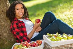 Mixed Race African American Girl Teenager Eating Apple by Tree. Beautiful happy mixed race African American girl teenager female young woman in an orchard eating Royalty Free Stock Images