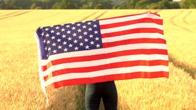 Mixed race African American girl teenager female young woman holding an American USA Stars and Stripes flag in a. 4K video clip of mixed race African American stock video footage