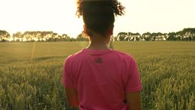 Mixed race African American girl teenager female young woman runner using smart watch and running on path through field of barley stock footage