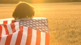 Mixed race African American girl teenager female young woman wrapped in an American US Stars and Stripes flag in. 4K video clip of mixed race African American stock video footage
