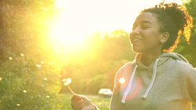 Mixed race African American girl teenager girl young woman blowing dandelion at sunset. 4K video clip of beautiful happy mixed race African American girl stock video