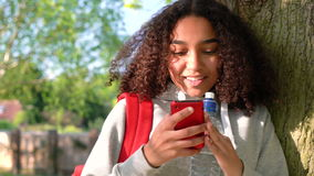 Mixed race African American girl teenager leaning against a tree using cell phone. 4K video clip of beautiful happy mixed race African American girl teenager