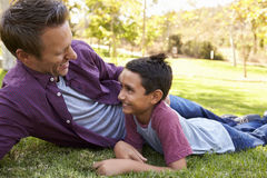 Mixed race Asian boy lying in a park with his white father Royalty Free Stock Image