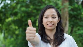 Mixed race Asian girl thumb up with nature background Stock Images