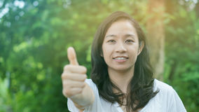 Mixed race Asian girl thumb up with nature background Stock Photos