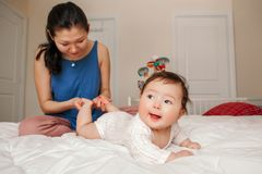 Mixed race Asian mother kissing touching embracing her newborn infant baby stock photography