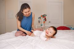 Mixed race Asian mother with newborn baby doing massage and physical exercises royalty free stock image