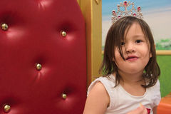 Mixed race Asian toddler with tiara on throne Stock Photography