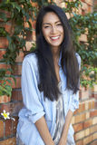 Mixed race Asian woman looks to camera, three quarter length Royalty Free Stock Images