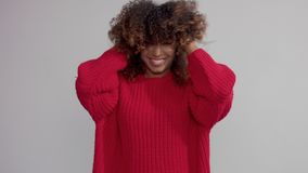 Mixed race black woman in studio with big curly hair shake it in slow motion. From 60 fps stock video
