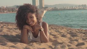 Mixed race black young woman outdoors, summer sunset light, beach zone of Barcelona. Lies on sand and watching to the camera smiling stock video footage