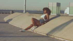 Mixed race black young woman outdoors, summer sunset light, beach zone of Barcelona. Panned video model sit on concrete skaters structure stock video