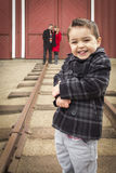 Mixed Race Boy At Train Depot With Parents Smiling Behind Stock Image