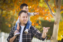Mixed-race Boy With Caucasian Father pointing and Riding on Shoulders Royalty Free Stock Photography