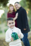 Mixed Race Boy Holding Gift In Front with Parents Behind Stock Photos