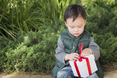 Mixed Race Boy Opening A Christmas Gift Outdoors Royalty Free Stock Images