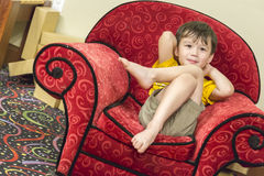 Mixed Race Boy Relaxing in Comfortable Red Arm-Chair Stock Photography
