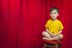 Mixed Race Boy Sitting on Stool in Front of Curtain Stock Photo
