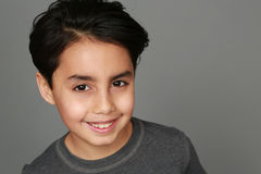 Mixed race boy smiling. Headshot of mixed race boy smiling on gray background Stock Photography