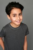 Mixed race boy smiling. Headshot of mixed race boy smiling on gray background Royalty Free Stock Images