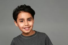 Mixed race boy smiling. Headshot of mixed race boy smiling on gray background Stock Images