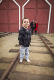 Mixed Race Boy at Train Depot with Parents Smiling Behind Stock Photo
