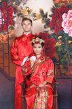 Mixed Race Bride and Groom in Studio wearing traditional Chinese wedding outfits Stock Images