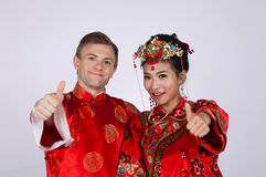 Mixed Race Bride and Groom in Studio wearing traditional Chinese wedding outfits Royalty Free Stock Photos