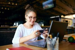 Mixed race business woman distracted from work on the laptop watching video on smartphone. Freelancer holding mobile royalty free stock image