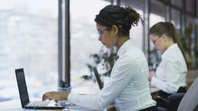 Mixed race business woman making notes, typing on laptop, hard-working manager. Stock footage stock video footage