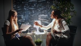 Mixed race business women discussing the text of contract in office while sitting at the table and drinking coffee. Mixed race business women discussing the text stock video