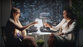 Mixed race business women talking to each other and making cheers with bocals of champagne. At the restaurant with skyscrapers in the background stock footage