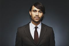 Mixed race businessman against black background. Portrait of confident and attractive male model in business suit looking at camera. Mixed race businessman Royalty Free Stock Image