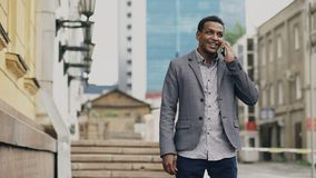 Mixed race businessman talking at smartphone and feels happy about making deal outdoors. Mixed race businessman talking at smartphone and feels happy and dancing Royalty Free Stock Photography