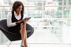 Mixed race businesswoman using digital tablet, full length royalty free stock photography