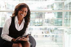 Mixed race businesswoman using digital tablet, to camera Royalty Free Stock Images